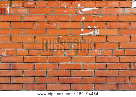 Brick wall with traces of pasted ads. Abstract background