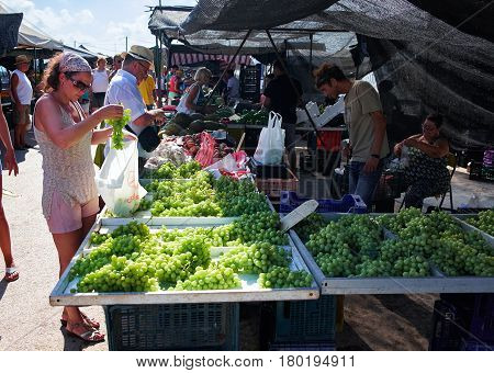 El Raso, Spain - July 11, 2015: The young woman at the village market buys grapes