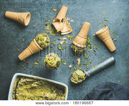 Homemade pistachio ice cream in ceramic mold and metal scooper with crashed pistachio nuts and waffle cones over grey concrete background, top view, selective focus
