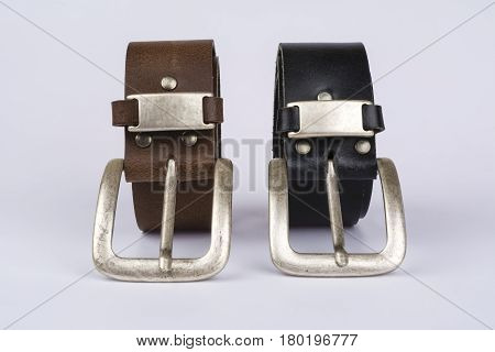 Two men's leather belt black and brown on a table on a white background