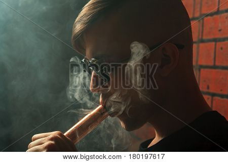 Vape. Young Handsome White Guy With Electronic Cigarette Lets Rings Out Of Steam. Vaping.