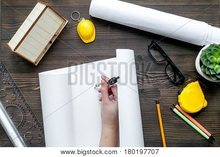 Architects workplace with constructor tools with hands and dlasses on wooden table background top view