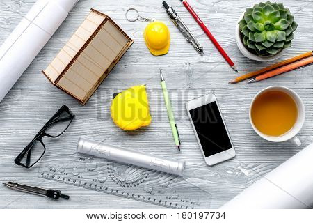 architect working desk with cup of tea, phone and glasses on light wooden background top view