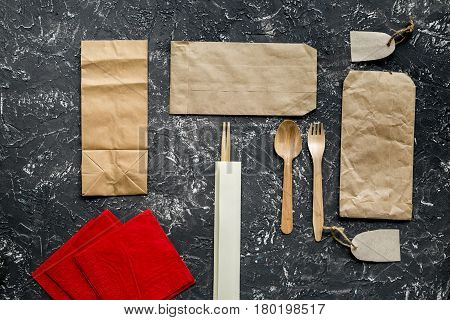 breakfast take away with flatware and paper bags on gray table background top view