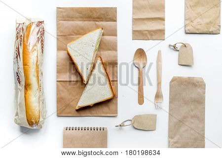 food delivery service workdesk with paper bags and sandwich on white background top view