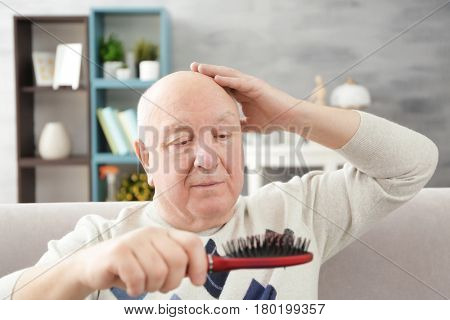 Senior bald man with hair brush at home