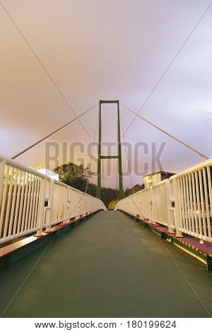 Pedestrian bridge of Pobena at night over the river Barbadun in the town of Muskiz Biscay Basque Country Spain. Long exposure at a cloudy night.