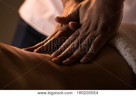 Massage closeup view with hands of professional masseur. Charming lighting