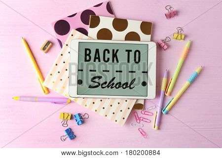 Tablet with BACK TO SCHOOL message and stationery on pink wooden background