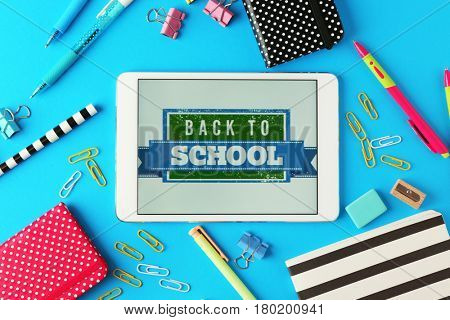 Tablet with BACK TO SCHOOL message and stationery on blue background