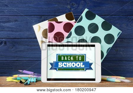 Tablet with BACK TO SCHOOL message and stationery on wooden table