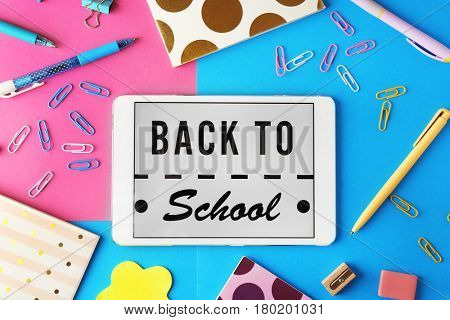 Tablet with BACK TO SCHOOL message and stationery on color background