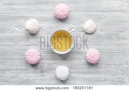 woman table trendy design with cup of tea and marsh-mallow in soft light on wooden table background top view pattern