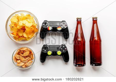 snacks for playing video games with joypad and beer on white desk background top view