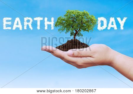 Earth Day concept. Male hands holding a tree with cloud shaped Earth Day text on the sky