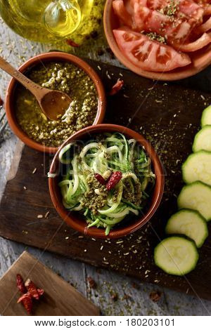 high-angle shot of some earthenware bowls with zucchini spaghetti, italian pesto sauce and chopped tomato, and a cruet with olive oil on a rustic wooden table