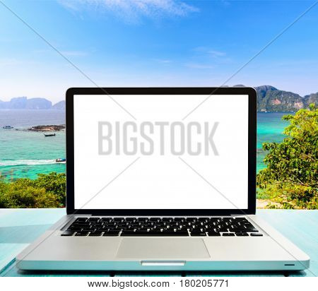 Modern laptop on blue wooden table with blank screen at tropical beach