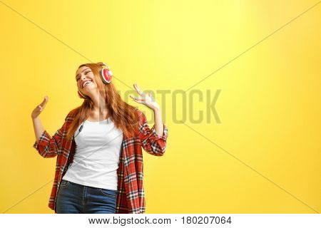 Beautiful young woman listening to music on color background