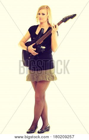 Music concert and show. Blonde pretty woman artist playing rock roll on electrical guitar. Young girl feels like star. Star beginner creating sounds song.