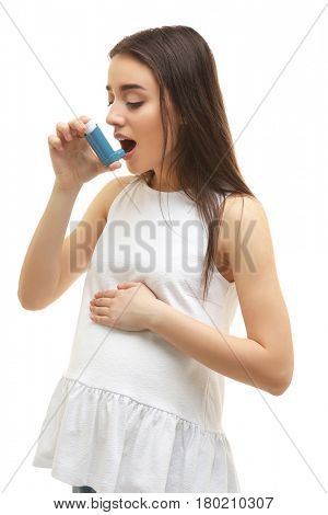 Young pregnant woman using inhaler during asthmatic attack, on white background