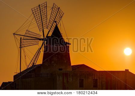 Windmill at sunset at the saltpans of Marsala in Sicily