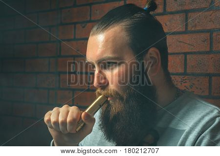 Vape. Young Brutal White Guy With Large Beard And With Electronic Cigarette.