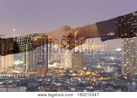 Double exposure of handshake and city night backgrounds