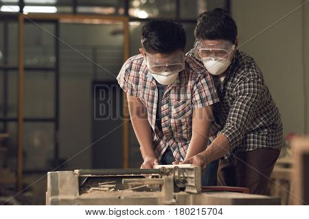 Father helping his son to cut wooden plank with band saw