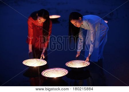 Women's in Ao dai Vietnam traditional dress are spot lamp in the river