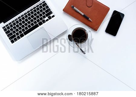 Modern White office desk table with laptop computerleather notebookpensmart phone and cup of coffee.Top view with copy space.Working desk table concept.