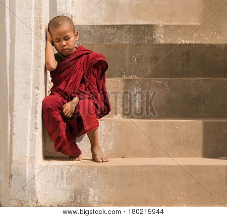 Little monk stay in pagoda MandalayMyanmar. Little monk or novice monk sitting in pagoda mandalay myanmar.