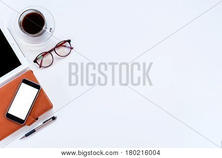 Modern White office desk table with tablet computerleather notebookpensmart phone and cup of coffee.Top view with copy space.Working desk table concept.