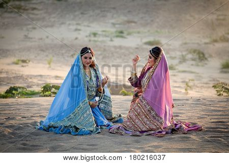 Persia or Iran Women's sitting talking joyful and relaxing on sand or Beach.