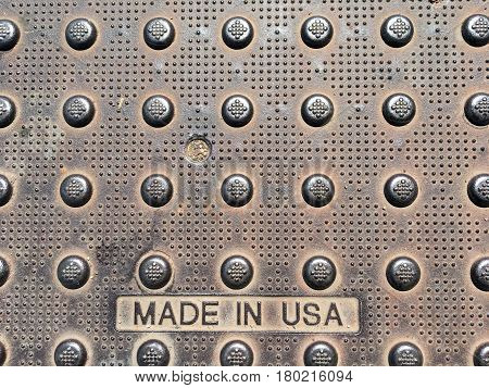 Weathered street steel cover plate with two words reading MADE IN USA in capital