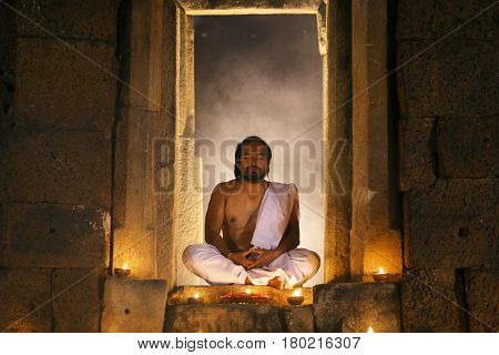 Priest or Yogi are sitting meditating in Ancient ornate huts made of stone or archaeological sites.