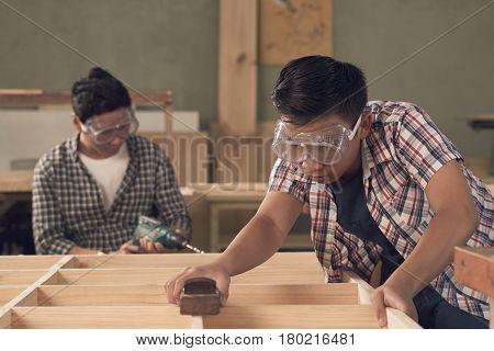 Vietnamese boy measuring wooden dresser in workshop
