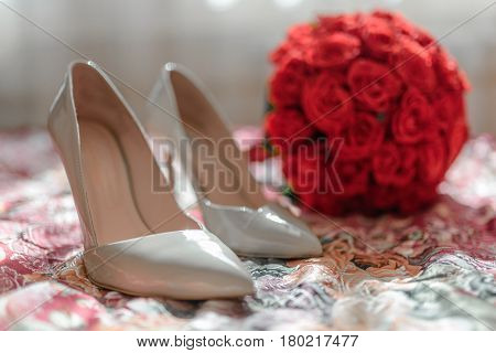 The composition in which the main details of the wedding day are gathered: Bride's bouquet Beige bride shoes and in the background is more visible wedding bouquet