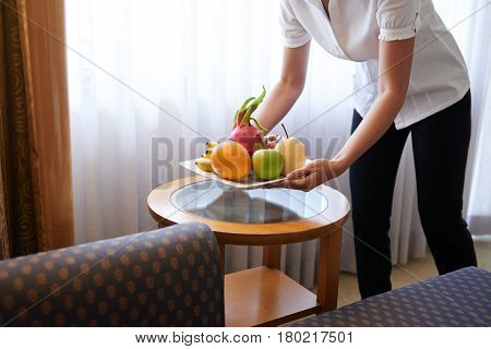 Maid bringing fresh fruit to the suite