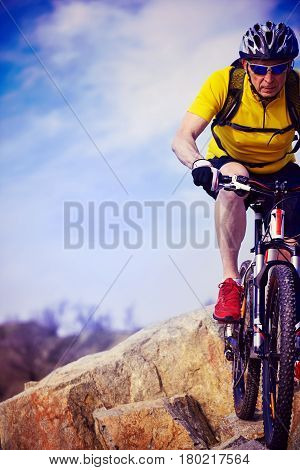Cyclist in helmet with mountain bike in the mountains.