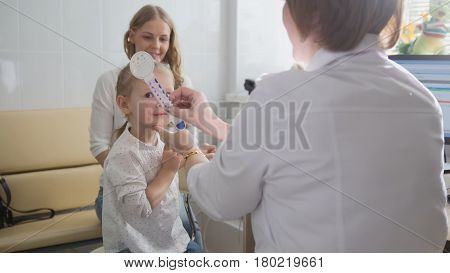 Little cute blonde girl in child's ophthalmology - optometrist diagnosis eyesight, close up
