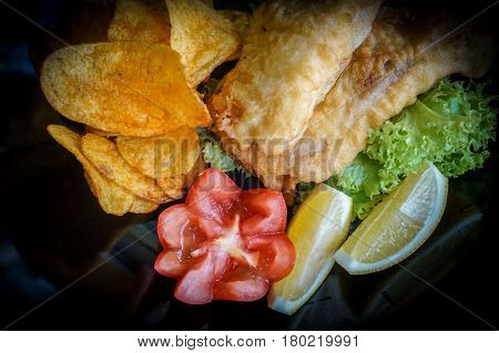 Close up of fish and chips served with a salad of garden-fresh lettuce,tomato and a piece of lemon deep fried battered fish on a plate.