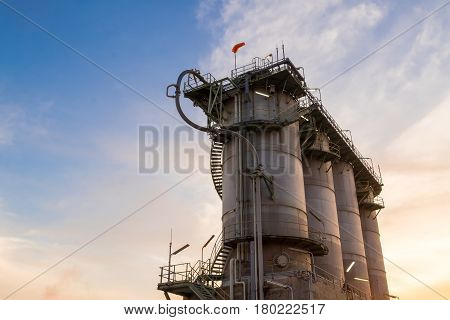 Silo on sunrise background, Storage plastic on sky background, Deliver resins to customers.