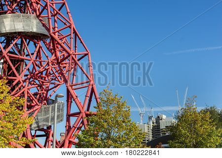 London, England - October 17, 2016;  From Queen Elizabeth Olympic Park in Stratford London abstract ArcelorMittal Orbit red tubular spiraling steel structure on one side of image with white construction cranes in distant city skyline.