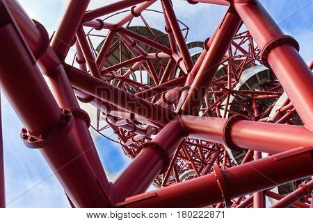 London, England - October 17, 2016; Looking up through the abstract structure of ArcelorMittal Orbit red tubular spiralling steel structure  at 114.5 metre is London's tallest sculpture a popular tourist attraction and observation tower in the Queen Eliza