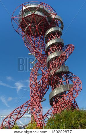 London, England - October 17, 2016; ArcelorMittal Orbit red tubular spiralling steel structure silver walkway and stainless slide contrasts with brilliant blue sky at 114.5 metre London's tallest sculpture a popular tourist attraction and observation towe