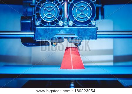 Modern 3D printer printing figure close-up macro.Automatic three dimensional 3d printer performs plastic pink and blue colors modeling in laboratory. 3d-printing processing with white background