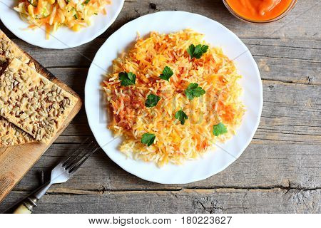 Basmati rice with vegetables and parsley on a plate, cabbage salad on a plate, fork, cookies with seeds, pumpkin sauce in bowl on old wooden table. Vegetarian lunch or dinner recipe. Top view