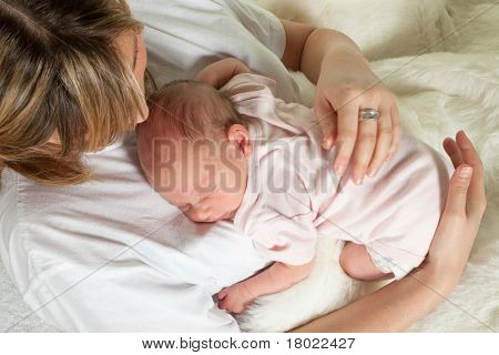 Young loving mother watching her sleeping 18 days old baby