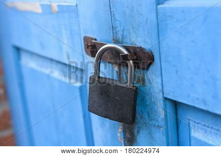 Blue wooden door of old abandoned house locked with padlock