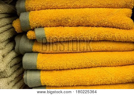 Home wardrobe with several yellow towels lying on shelf